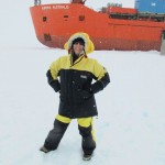 Wendy Sharpe on the sea ice with the Aurora Australis behind, picture courtesy Wendy Sharpe